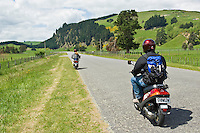 Two tourists on rental scooters on rural road, New Zealand