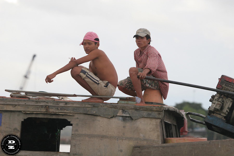 A boat pilot and passenger ride along on the Mekong Delta in Vinh Long, Vietnam.  The Mekong Delta has long been the watery  thoroughfare for the many villages that dot the riversides of the delta. Many of the villages have floating markets where people can buy produce and other items from wholesalers.  Photograph by Douglas ZImmerman
