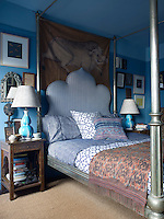 The master bedroom's vintage cloth painting, bed, and bedding are from John Robshaw Textiles; the lamps are by Christpher Splitzmiller and the walls and ceiling are painted in a Benjamine Moore's 'Kensington Blue and 'New Hope Gray'
