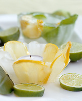 Homemade candle holders made of ice with citrus slices inside are a creative addition to the party decorations