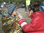Konstantina Koulouri, a volunteer with the Greek Red Cross, playfully pokes the nose of Hajem, a 2-year old Syrian refugee who just arrived on the Greek island of Lesbos. The boy was sopping wet from transiting the Aegean sea in a small boat with his family, so Koulouri wrapped him in insulating material to help him stay warm.