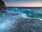 Beautiful sunrise over stormy waters of Georgian Bay hitting its rocky shore. Bruce Peninsula National Park, Ontario, Canada.