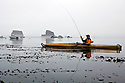 WA07065-00...WASHINGTON - Fly fishing from a kayak in the Straits of Juan De Fuca near Sail and Seal Rocks.