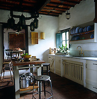 Terracotta floor tiles and exposed beams create a warm and cosy atmosphere in the kitchen of this Tuscan farmhouse