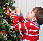 Little boy decorating a Christmas tree at home. Three year old child with Christmas ornament.