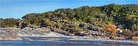 This daytime panorama of the Pedenrales River shows the amount of water flowing over the rocks at Pedernales Falls State Park. On the right is a lone cypress, orange with November color.