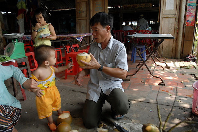 A vietnamese man cuts coconuts for his children in Can Tho, Vietnam.