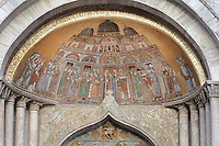 Mosaic of the procession of the relics of St Mark to St Mark's Basilica, c. 1270-75, above the St Alipius Gate, a lateral portal of St Mark's Basilica, or Basilica San Marco, Venice. This is the oldest mosaic in the building and the oldest representation of the basilica. It is also thought to represent crowds celebrating the crowning of a new doge. The basilica was consecrated 1084-1117 and was originally the chapel of the Doge, becoming the city's cathedral in 1807. The city of Venice is an archipelago of 117 small islands separated by canals and linked by bridges, in the Venetian Lagoon. The historical centre of Venice is listed as a UNESCO World Heritage Site. Picture by Manuel Cohen