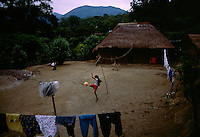 Children play in the courtyard in front of their traditional thatched-roof adobe home in Palictla, Mexico. South of Ciudad Valles the road passes through Huasteca Indian country. At one time the Huastec population was once estimated to be one million, but today they number about 150,000. <br />