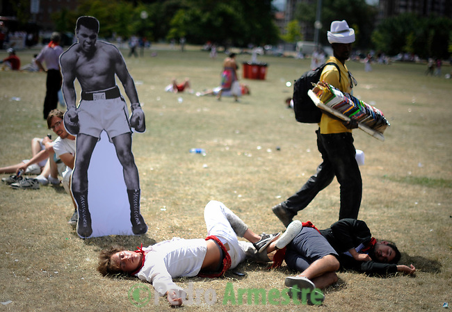 An image of boxer Muhammad Ali is placed for the creatives in front of people sleeping in parks during the Festival of San Fermin, 8 July 2012, in Pamplona, northern Spain. The festival is a symbol of Spanish culture that attracts thousands of tourists to watch the bull runs despite heavy condemnation from animal rights groups . (c) Pedro ARMESTRE