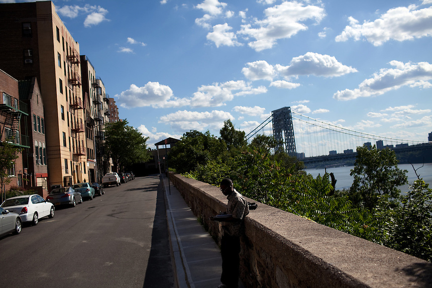 An artist at work on 187th street overlooking the Hudson with the George Washington Bridge in the background in Manhattan, NY on June 23, 2012.