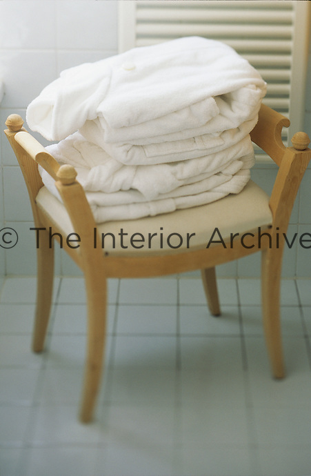 A pair of fluffy white robes ready for guests on a stool at the Daniela Steiner Spa in the Dolomites