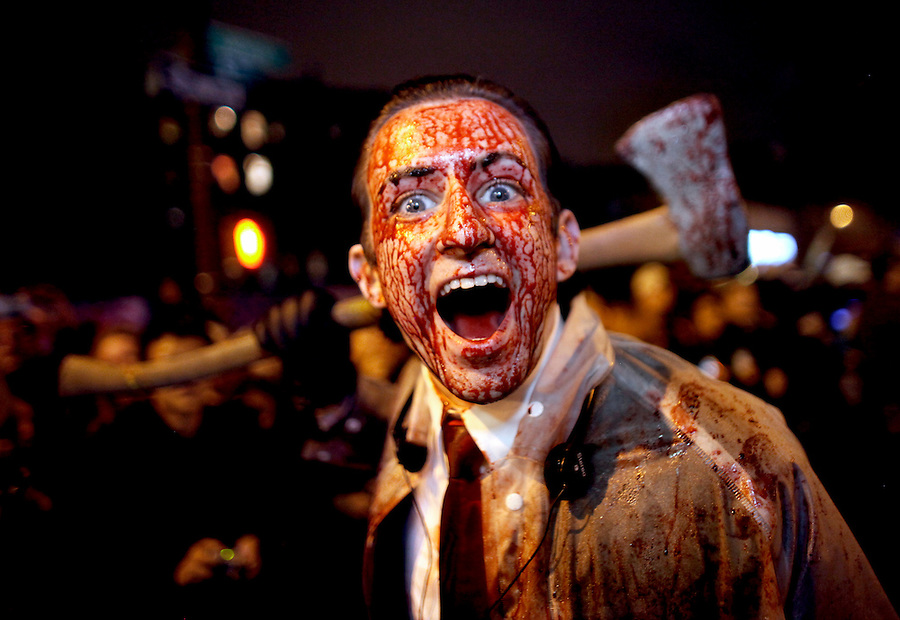 A man is drenched in fake blood as he wields an ax in the annual Greenwich Vilage Halloween Parade in New York.