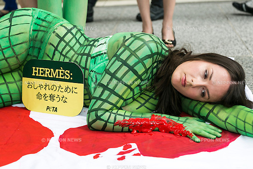 A body painted model from PETA (the People For The Ethical Treatment of Animals organization) poses as slaughtered crocodiles in front of the luxury Hermes store in the upscale Ginza shopping district on July 30th, 2015 in Tokyo, Japan. PETA claims that Hermes bags and accessories use crocodiles and alligators that are kept in poor conditions and still conscious when being cut open. Japan is a big market for Hermes and luxury brands with many Asian tourists and Japanese visiting Ginza for shopping. (Photo by Rodrigo Reyes Marin/AFLO)