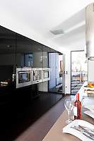 A wall of elegant black cupboards of high-gloss parapan complements the mellow grey of the Quartz stone used in the construction of the long kitchen island