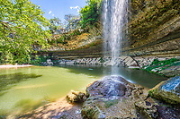 Another image of Hamilton Pool waterfall located outside of Austin Texas. The is a natural pool created by an underground river that collasped and formed by erosion over  thousand years.  The erosion created this cave with stalactite growing from the celling, a waterfall flowing over the limestone along bolders along with moss along with emerald green swimming hole.  The preserve includes about 232 acres of natural habitat and is home to the golden cheek warble.   This place draws a lot of people want to enjoy this place on a hot summer days but if you want to come be sure and call ahead and make reservation.  Over the years the place has been loved to death and you now need a reservation just to get in also it is also good to make sure it is open for swimming because it is a natural swimming hole no chemicals are added to the water so at times it get shut down due to high bateria counts.  This nature preserver is part  of the  Balcones Canyonlands Preserve and is a protected environment.