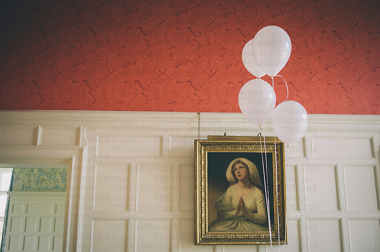 Old painting hanging on a wall in a panelled room with white balloons