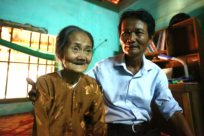 """Nguyen Tan Hoa, 55, sits with his mother, 85-year-old Nguyen Thi Tien, in his boyhood home in the village of Tam Hoa, about 25 miles southwest of Da Nang, Vietnam. Nguyen was around 10-years-old when a squad of Marines moved into his village under the Combined Action Program, a pacification effort designed to train local militia and keep Viet Cong guerrillas from taking over. """"As soon as I saw them, I wanted to be a Marine,"""" he says. He spent much of his free time hanging out at the Marines' compound, and they adopted him into the unit. He says the Marines would often come to his mother's shop to buy snacks and drinks. When the Americans left in 1975, """"I really felt like I was the last G.I. in Vietnam,"""" he says. May 12, 2012."""