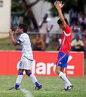 Diego Galdamez (8) of El Salvador grimaces after losing as David Acuan (4) of Costa Rica celebrates during the group stage of the CONCACAF Men's Under 17 Championship at Jarrett Park in Montego Bay, Jamaica. Costa Rica defeated El Salvador, 3-2.