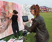 "Joanna Layla (www.joannalayla.com), artist, being filmed on an iPad whilst taking part in ""Showtime"", part of the London 2012 Festival of Arts to celebrate the London Olympics.  A family fun spectacle including dance, painting, music, acrobatics and some large mobile dynosaurs walking amongst the crowd.  On Blackheath Common, Saturday August 4th and funded by the Mayor of London and Arts Council England."