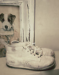 Old baby shoes sits on an old table in front of a picture of a dog.