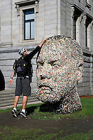 Young man placing chewing gum on Gumhead sculpture by Douglas Coupland outside the Vancouver Art Gallery, Vancouver, BC, Canada