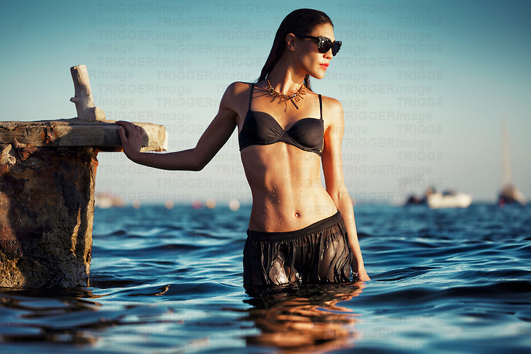 Caucasian female model wearing black swimwear and sunglasses standing outdoors in summer in water