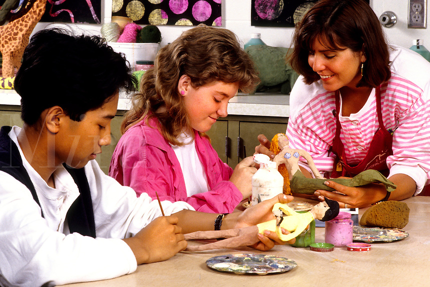 Student girls age 13 in Eighth grade learning art with teacher helping at schoo