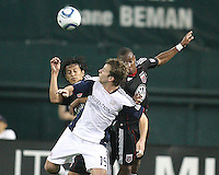 Juan Manuel Pena #3 and Rodney Wallace #22 of D.C. United go up for a header against Zack Scilawski #15 of the New England Revolution during an MLS match on April 3 2010, at RFK Stadium in Washington D.C.