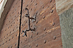 Old door with bolts and a handle in the shape of a dragon in Tirano, Italy