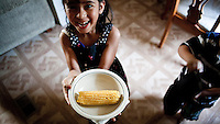 Wendy, the daughter of Mexican immigrants, with cooked corn in her trailer home, in Garden City, Kansas. This is home to many migrant workers who have come to the town to work at the Tyson meat packing plant. The Tyson facility kills and processes between five and six thousand beef cattle every day. Kansas dominates the American beef industry, producing 25% of all beef raised in the USA. However, the industry is heavily dependent on cheap immigrant labour.