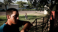 A child plays in the garden of a trailer park, in Garden City, Kansas. The area is home to many migrant workers who have come to the town to work at the Tyson meat packing plant. The Tyson facility kills and processes between five and six thousand beef cattle every day. Kansas dominates the American beef industry, producing 25% of all beef raised in the USA. However, the industry is heavily dependent on cheap immigrant labour.