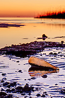 An antique bottle washed the on Kitty Hawk Bay, photographed at sunset.