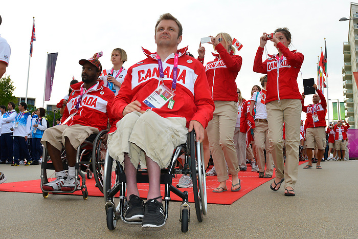 London, England 26/08/2012 - Abdi Dini and Robert Hedges of Wheel Chair Basketball enter the Paralympic Village Plaza during the flag raising ceremony at the London 2012 Paralympic Games. (Photo: Phillip MacCallum/Canadian Paralympic Committee)