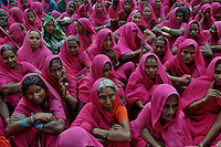 Gulabi Gang members during a meeting. Sampat Pal Devi the commander of Gulabi Gang fights for women empowerment, justice and rights among the poor people of Bundelkhand region of Uttar Pradesh. Sampat Pal Devi comes from a poor family in Bundelkhand - the poorest region of India. The region is fraught with abject poverty, gross under development, lack of law and order, and stark casteism in which the Brahmins and other higher caste people treat their low caste brethren with disdain. Out of such situation when Sampat Pal Devi decided to speak up for the poor, she has been winning heart felt gratitude of the poor as well as enmity of the high caste people and grudging respect of the law enforcement officials who used to be largely inactive in these badlands of North India. Initially, she began with helping distressed women - victims of domestic violence and dowry system, but soon started getting other cases of nature of land dispute and under development. She emerged as a fiery leader in 2007, when she beat up the OC of the local police station while demanding release of a dalit woman kept locked up in the cell for thirteen days without being charged with a case.Today, she has a huge fan following of some 25 hundreds of thousands of women (spread across 8 districts of the state of UP) who have come to be known as Gulabi Gang or Pink Vigilante Women for their vibrant pink sarees - the costume of the gang; and fiery nature of dealing with injustice. When verbal negotiations for justice fail they resort to beating up. Sampat Devi is viewed as a messiah with the promise of bringing back law and order for the poor, in these mafia troubled areas. Today, perpetrators are simply scared of her as she does not hesitate to challenge law and order and even system - to win justice for the poor. More complaints related to domestic violence and other problems are registered now with the police than they ever used to be. She being one of the Other Backward Caste people in the region