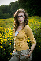 Young woman wearing eyeglasses standing in open meadow