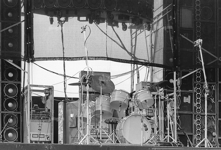 Bill Kreutzmanns Drum Set at the Grateful Dead Concert at Dillon Stadium on 31 July 1974. Taken before the show. In this view, gear racks, dual cancelling microphones, speaker stacks, vocal speaker array, wind scrim, etc etc