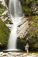 A woman at Dorothy Falls near Lake Kaniere near Hokitika - West Coast, New Zealand