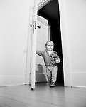 Child walks through an open door, portrait (B&W)