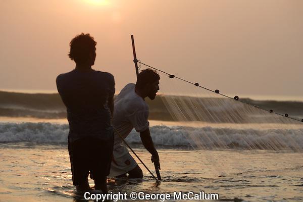 Pair of Beach fishermen pulling one end of Gill net through surf, Goa, Arabian sea, India
