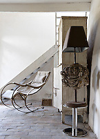 In one corner of the entrance hall are a cantilevered metal rocking chair, a white-painted wooden cupboard and a standard lamp constructed from a melange of bric-a-brac