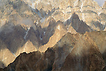 The bands of light crossing the face of this peak accentuate the natural bands of colored rock, forming a mosaic of color, Pasu Peak, Karakoram Range, Pakistan.