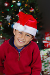 Boy with Santa Hat in front of Christmas tree with lights and decorations