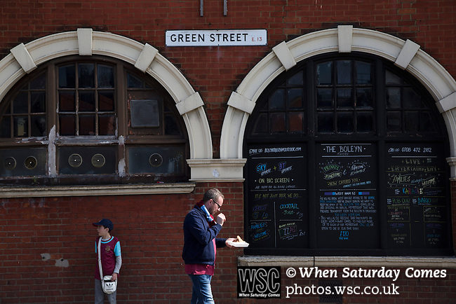 West Ham United 2 Crystal Palace 2, 02/04/2016. Boleyn Ground, Premier League. A man eating a snack walking past the Boleyn Tavern on Green Street, close to the Boleyn Ground before West Ham United hosted Crystal Palace in a Barclays Premier League match. The Boleyn Ground at Upton Park was the club's home ground from 1904 until the end of the 2015-16 season when they moved into the Olympic Stadium, built for the 2012 London games, at nearby Stratford. The match ended in a 2-2 draw, watched by a near-capacity crowd of 34,857. Photo by Colin McPherson.