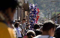 A vendor sells toys depicting members of a Catholic brotherhood during the Procesión de Jesús Nazareno de La Caída from Iglesia San Bartolomé Becerra in Antigua, Guatemala. Each weekend during Lent features a procession by a different church, culminating in Semana Santa, or Holy Week, one of the largest Easter commemorations in Latin America.