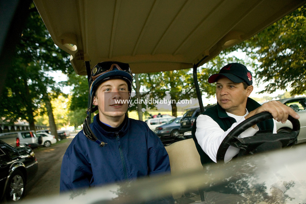Jockey Julien Leparoux (L) rides back on a golf cart with his agent Steve Bass to the Biancone stable in Saratoga Springs, NY, United States, after an early morning breeze, or moderate speed workout ride, 5 August 2006.