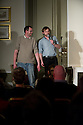 """Harrogate, UK. 20.3.12. Sitting Room Comedy at the St George Hotel hosts the legendary Arthur Smith with support from Naz Osmanoglu. Picture shows Naz Osmanoglu (on stage) standing next to 6' 9"""" Danny (on the floor). Photo credit: Jane Hobson."""