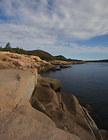 The rugged shoreline highlights the drive along Park Loop Road in Acadia National Park, Maine. In the distance is Sand Beach  and Gorham Mountain (525 ft.) and The Beehive (520 ft.) and are brightened with fall color.