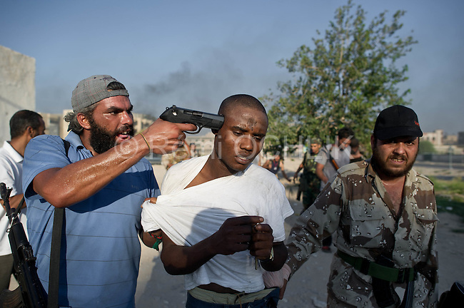Remi OCHLIK/IP3 PRESS - On august, 25, 2011 In Tripoli - Rebels fighters in Abu Slim neighborhood against the last resistance of the Gadaffi loyalist forces. They captured some african people supposed to be Gadaffi mercenaries and snippers.