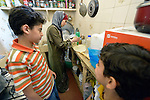 As two of her children look on, Ahlam Mazatha prepares food in her kitchen in Madaba, a sprawling Palestinian refugee camp in Jordan that has grown in recent years with the arrival of refugees--like Mazatha--from war-torn Syria. She and her husband and three children fled Daraa in 2013 when bombing destroyed their home. Mazatha was a teacher in Syria, and her husband was a librarian and owned a taxi, but in Jordan they are not allowed to work by the government. The  Department of Service for Palestinian Refugees of the Middle East Council of Churches, a member of the ACT Alliance, provides a variety of services here, including medical care.